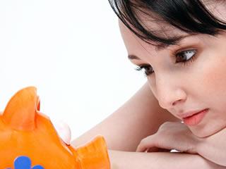 ブタの貯金箱とにらめっこする女性