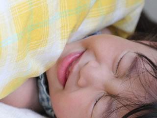 黄色い布団で休む熱が出て具合が悪い子供
