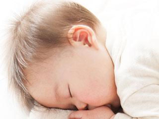 布団に顔をつけて寝る赤ちゃん