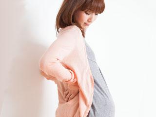 立って下を見る妊婦