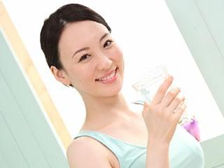 朝から運動して水分補給をする元気な女性