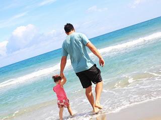 父親と子供が遊ぶ風景を撮影する母親