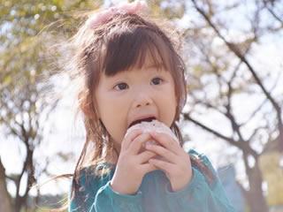 ピクニックのお弁当を楽しそうに頬張る子供