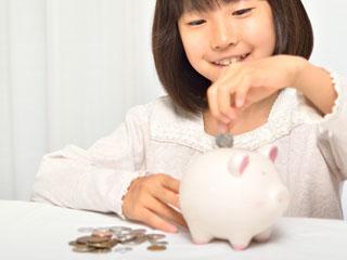 ブタの貯金箱に硬貨を入れる女の子