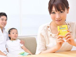 電卓を持つ母親と背後の子供