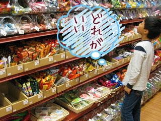 駄菓子屋の商品の前に立つ子供