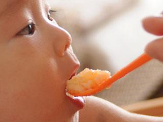スプーンで食事する赤ちゃん