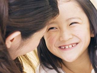 笑顔の子供と向かい合う母親