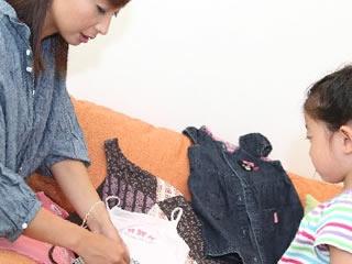 一緒に洗濯物をたたむ親子