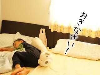 朝日が射す部屋で寝る子供