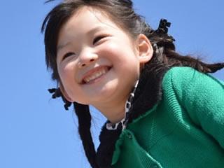 晴天の空と可愛い笑顔を振りまく子供