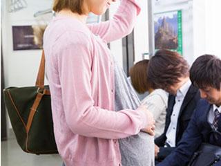 電車でつり革につかまる妊婦