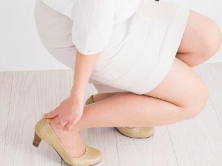 足首を押さえる女性