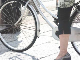 歩道で止まる女性が乗った自転車
