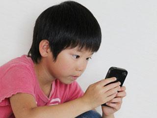 携帯ゲームをする子供