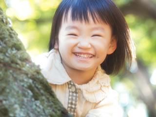 木陰から顔を覗かせる笑顔の女の子