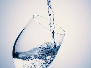 天然水が上から注がれるグラス