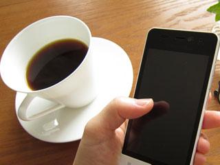 スマホを持つ手とコーヒーカップ