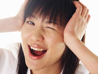 頭を押さえて嬉しそうな女性