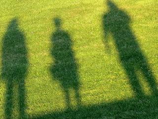 芝生の多い公園に遊びに来た親子の影