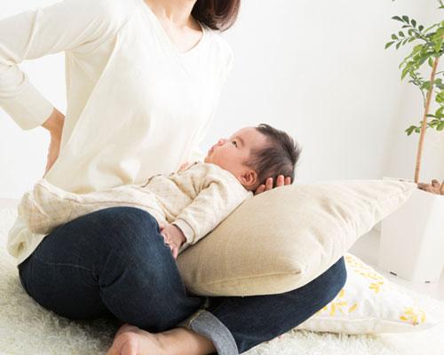 赤ちゃんを膝にのせた母親