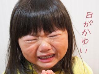 目を閉じて涙をこぼす子供