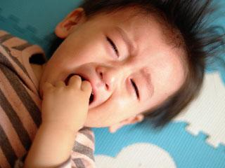 泣き顔の幼児が指を咥える
