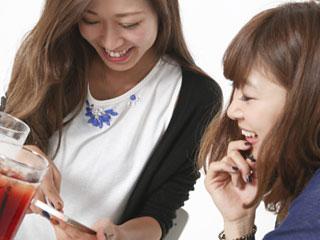 女性二人がスマホを見ながら会話