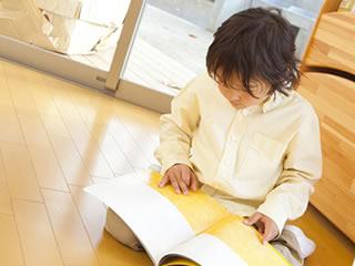 幼稚園で一人ママのお迎えを待ちながら本を読む子供