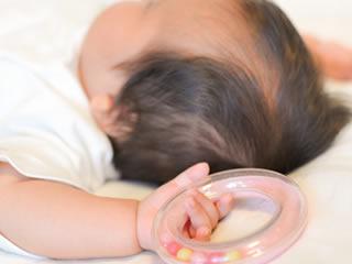 左手にお気に入りのおもちゃを持った病気がちな赤ちゃん