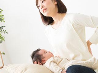 赤ちゃんをひざに載せて腰に手をやる母親