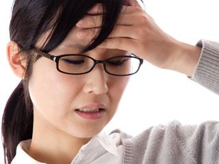 額を手で押さえながら疲れた表情の女性
