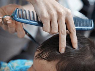 美容室で髪カットされる赤ちゃん