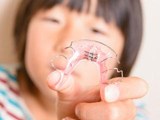 矯正器具を見せる子供
