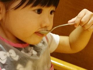 スプーンで食事する子供