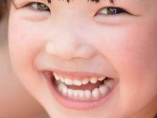 白い歯を見せて笑う女の子
