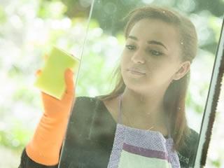 水垢汚れが頑固な大きな窓の掃除をする女性
