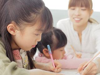 指導員が児童の勉強をみている