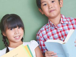 本を持って立つ男の子と女の子