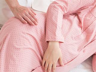 妊婦の腰に手を置く助産師