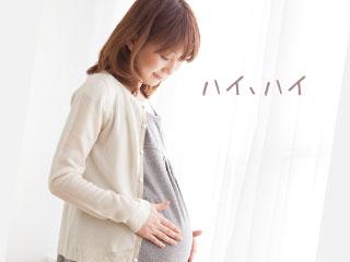 お腹を触りながら話しかける妊婦