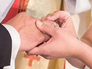 愛する夫に結婚の証の指輪をはめる妻