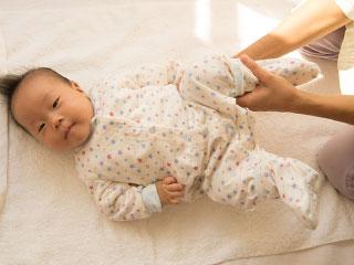 赤ちゃんの脚を掴んで動かす女性