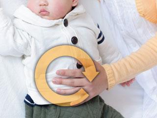 赤ちゃんのお腹の上に掌を置く母親