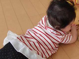床に寝そべる赤ちゃん
