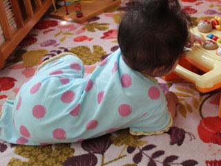ずりばいして玩具に触る赤ちゃん