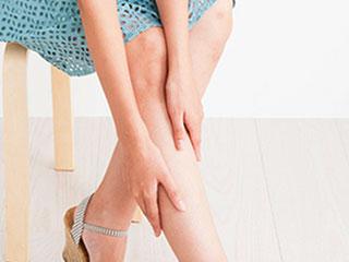 脚を両手で揉む女性