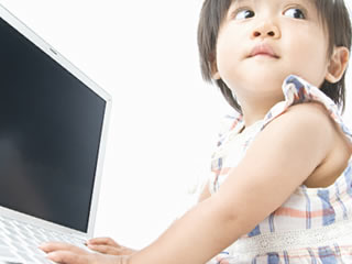離婚した母親の代わりにパソコンで養育費について調べる子供