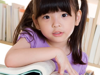 離婚後の養育費の支給額と期間を本で調べる子供