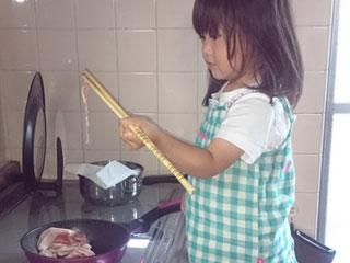 フライパンに肉を入れる女の子